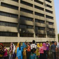 Photo - Workers stand outside an 11-story building that houses the Tung Hai Sweater Ltd. factory and apartments after a fire in Dhaka, Bangladesh, Thursday, May 9, 2013.  The fire broke out in the building Wednesday night, not long after the up to 300 workers of the factory went home for the day, killing at least eight people officials said Thursday. (AP Photo/Ismail Ferdous)