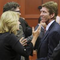 Photo - Attorney Mark O'Mara is congratulated by his wife Jen after Zimmerman's not guilty verdict was read in Seminole Circuit Court in Sanford, Fla. on Saturday, July 13, 2013. Jurors found Zimmerman not guilty of second-degree murder in the fatal shooting of 17-year-old Trayvon Martin in Sanford, Fla. (AP Photo/Joe Burbank, Pool)