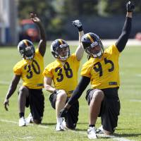 Photo - Pittsburgh Steelers first round draft choice, linebacker Jarvis Jones , front, out of Georgia,  stretches with free agent safety Andrew Taglienetti (38) from Pittsburgh, and fifth round draft choice cornerback Terry Hawthorne from Illinois, during NFL football rookie minicamp on Friday, May 3, 2013 in Pittsburgh. (AP Photo/Keith Srakocic)