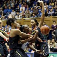 Photo - Duke's Chelsea Gray, center, drives to the basket against Maryland's Alyssa Thomas, left, and Alicia DeVaughn during the first half of an NCAA college basketball game in Durham, N.C., Monday, Feb. 11, 2013. (AP Photo/Gerry Broome)