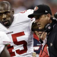 """Photo -   File - In this Aug. 18, 2012, file photo, San Francisco 49ers' Brandon Jacobs (45) is helped off by head coach Jim Harbaugh in the first quarter of an NFL preseason football game against the Houston Texans in Houston. Jacobs has posted advice on Twitter with a reference to never working """"in a place where you hate your boss so much."""" The hash tag: """"YouLiveAndYouLearn."""" Jacobs had terrible timing with the tweet Thursday, Nov. 15, 2012, considering coach Harbaugh was hospitalized for what the team called a """"minor procedure"""" for an irregular heartbeat. In the locker room soon after his post, Jacobs said people shouldn't """"assume"""" his remarks were football-related, then followed up with more tweets. He made one post saying that """"football is not my life."""" (AP Photo/David J. Phillip, File)"""