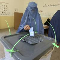 Photo - An Afghan woman casts her vote at a polling station in Jalalabad, east of Kabul, Afghanistan, Saturday, June 14, 2014. Afghans choose a new president Saturday in a runoff election between two candidates who both promise to improve ties with the West, combat corruption and guide the nation with a steadier hand than outgoing leader Hamid Karzai. (AP Photo/Rahmat Gul)