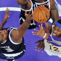 Photo - Oklahoma City Thunder power forward Serge Ibaka (9), of the Republic of Congo, and Los Angeles Lakers center Dwight Howard (12) reach for a rebound during the first half of their NBA basketball game, Sunday, Jan. 27, 2013, in Los Angeles. The Lakers won 105-96. (AP Photo/Reed Saxon) ORG XMIT: LAS201