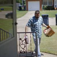 Photo - Greg Ross carries groceries into his house Friday in Oklahoma City. Ross has taken on a second job to make up for lost income after he and thousands of other federal employees were forced to take furlough days because of federal budget cuts.  BRYAN TERRY - THE OKLAHOMAN