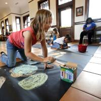 Photo - Cetani Lenker, 9, chooses her colors for a chalk art contest at the Santa Fe Depot in Norman. The children's art contest was held as a prelude to the annual CROP Walk to Stop Hunger. The Norman walk is Sunday.