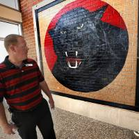 """Photo - Plaza Towers Elementary School Principal Patrick Chase stands in front of a wall section of the old school building that contained a painting of the mascot """"Paws."""" on Tuesday, Aug. 12, 2014 in Moore, Okla. The wall was salvaged and built into the entryway of the new Plaza Towers Elementary School.  Photo by Steve Sisney, The Oklahoman"""