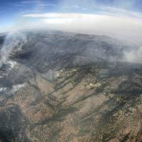 Photo -   In this aerial photograph made using a fisheye lens, the Lower North Fork Wildfire burns near the foothills community of Conifer, Colo., southwest of Denver on Tuesday, March 27, 2012. Firefighters are now able to actively battle the blaze on the ground that started on Monday and has already destroyed at least 16 homes in the rugged terrain. (AP Photo/David Zalubowski)