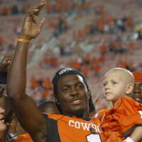 Photo - FILE -    OSU / CELEBRATION: In this Saturday, Sept. 26, 2009, file photo, Oklahoma State University wide receiver Dez Bryant is pictured as he celebrates with cancer patient Cason Tacket, right,  the Cowboys 56-6 win over Grambling State in an NCAA college football game in Stillwater, Okla. Bryant has been ruled ineligible by Oklahoma State for an improper interaction with a former NFL player. (AP Photo/Brody Schmidt, File) ORG XMIT: OKSO108