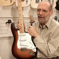 Photo - George Gruhn poses with the first production model Fender Stratocaster guitar, Tuesday, March 18, 2014, in Nashville, Tenn. The sunburst-finish Strat bears the serial number 0100. Although some Strats have lower numbers that begin with 0001, Gruhn says they actually were manufactured later in that first year of production. (AP Photo/Kristin M. Hall)