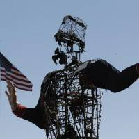 Photo - The burned remains of Big Tex stand at the State Fair of Texas Friday, Oct. 19, 2012, in Dallas. Fire destroyed Big Tex on Friday, leaving behind little more than the metal frame of the 52-foot-tall metal-and-fabric cowboy that is an icon of the State Fair of Texas. AP Photo