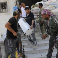 Photo -   In this Tuesday, July 31, 2012 photo, Free Syrian Army soldiers loot a police station in Aleppo, Syria. (AP Photo/Alberto Prieto)