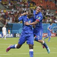 Photo - Italy's Mario Balotelli (9) celebrates with Italy's Marco Verratti (23) after Balotelli scored his side's second goal during the group D World Cup soccer match between England and Italy at the Arena da Amazonia in Manaus, Brazil, Saturday, June 14, 2014.(AP Photo/Marcio Jose Sanchez)