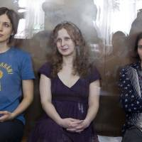 Photo -   FILE In this Wednesday, Aug. 8, 2012 file photo feminist punk group Pussy Riot members, from left, Nadezhda Tolokonnikova, Maria Alekhina and Yekaterina Samutsevich sit in a glass cage at a court room in Moscow, Russia. Three members of Pussy Riot were jailed in March and charged with hooliganism motivated by religious hatred after their punk performance against President Putin in Moscow's main cathedral. Theyare awaiting the verdict on Friday, Aug. 17, 2012. (AP Photo/Misha Japaridze, file)
