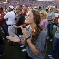 Photo - Whitney Hand applauds the introduction of her quarterback husband before a college football game between the University of Oklahoma Sooners (OU) and the Kansas State University Wildcats (KSU) at Gaylord Family-Oklahoma Memorial Stadium, Saturday, September 22, 2012. Photo by Steve Sisney, The Oklahoman  STEVE SISNEY - THE OKLAHOMAN