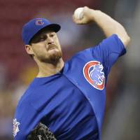 Photo - Chicago Cubs starting pitcher Travis Wood throws against the Cincinnati Reds in the first inning of a baseball game, Tuesday, Aug. 26, 2014, in Cincinnati. (AP Photo/Al Behrman)