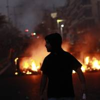 Photo - A protester walks in front of a burning barricade, during a protest after the stabbing of a 34 year old man in the suburb of Keratsini near Athens , Wednesday, Sept. 18 2013.  Violent clashes broke out Wednesday in several Greek cities after a member of the country's far-right Golden Dawn party was arrested in the fatal stabbing of a 34-year-old musician described as an anti-fascist activist. The stabbing drew condemnation from across Greece's political spectrum and from abroad. While the extremist Golden Dawn has been blamed for numerous violent attacks in the past, the overnight stabbing is the most serious violence directly attributed to a member so far. (AP Photo/Kostas Tsironis)