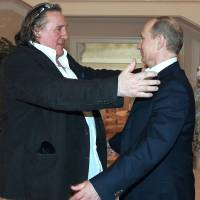 Photo - French actor Gerard Depardieu, left, greets Russian President Vladimir Putin after his arrival late Saturday, Jan. 5, 2013, at the president's residence in Sochi, the host city of the 2014 Winter Olympics. Depardieu has received a Russian passport after flying to Russia for a late night dinner with Putin. Depardieu sought Russian citizenship as part of his battle against a proposed super tax on millionaires in France, and Putin granted his request last week. (AP Photo/RIA-Novosti, Mikhail Klimentyev, Presidential Press Service)