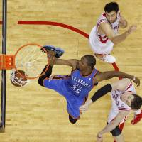 Photo - Oklahoma City's Kevin Durant (35) goes between Houston's Carlos Delfino (10) and Omer Asik (3) for a dunk during Game 4 in the first round of the NBA playoffs between the Oklahoma City Thunder and the Houston Rockets at the Toyota Center in Houston, Texas,Sunday, April 29, 2013. Oklahoma City lost 105-103. Photo by Bryan Terry, The Oklahoman