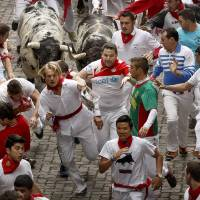 Photo - Revelers run with Torrestrella ranch fighting bulls during the running of the bulls of the San Fermin festival, in Pamplona, Spain, Monday, July 7, 2014. Revelers from around the world arrive in Pamplona every year to take part on some of the eight days of the running of the bulls glorified by Ernest Hemingway's 1926 novel