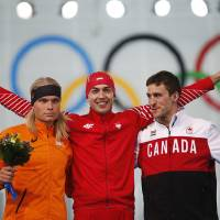 Photo - From left to right, silver medallist Koen Verweij of the Netherlands, gold medallist Poland's Zbigniew Brodka and bronze medallist Canada's Denny Morrison stand on the podium during the flower ceremony for the men's 1,500-meter speedskating race at the Adler Arena Skating Center during the 2014 Winter Olympics in Sochi, Russia, Saturday, Feb. 15, 2014. Verweij lost the gold medal by three thousandth of a second. (AP Photo/Pavel Golovkin)