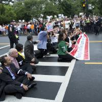 Photo - FILE - This Aug. 1, 2013 file photo shows immigration reform supporters blocking a street on Capitol Hill in Washington. For many House conservatives, President Barack Obama's decision to delay a central provision of his health care law has emerged as a major stumbling block _ not to health coverage, but to an immigration bill.  (AP Photo/Manuel Balce Ceneta, File)