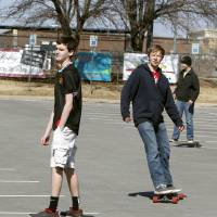 Photo - Below: Brothers Chris Taylor, left, Thomas  Taylor and Spencer  Taylor, use the wind  and sloped parking lot Monday to enjoy some skateboarding at Hafer Park in Edmond.  Photo By Paul Hellstern,  The Oklahoman