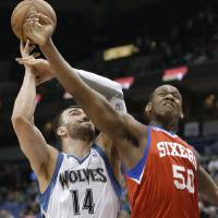 Photo - Philadelphia 76ers' Lavoy Allen, right, breaks up a scoring attempt by Minnesota Timberwolves' Nikola Pekovic, of Montenegro, in the first quarter of an NBA basketball game Wednesday, Feb. 20, 2013, in Minneapolis. (AP Photo/Jim Mone)