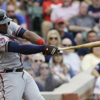 Photo - Atlanta Braves' Justin Upton hits a three-run double against the Chicago Cubs during the fourth inning of a baseball game in Chicago, Saturday, July 12, 2014. (AP Photo/Nam Y. Huh)