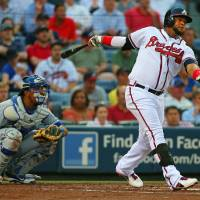 Photo - Atlanta Braves Juan Francisco hits a solo home run with Kansas City Royals catcher Salvador Perez looking on during the second inning of a baseball game Tuesday, April 16, 2013, in Atlanta.  (AP Photo/Atlanta Journal-Constitution, Curtis Compton)