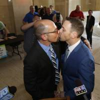 Photo - Rich Gillard, left, and Andrew Petroll kiss after their marriage ceremony at the Milwaukee County Courthouse on Friday, June 6, 2014, in Milwaukee. Earlier Friday, a federal judge struck down the state's ban on gay marriage. (AP Photo/Jeffrey Phelps)