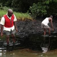 Photo - FILE - In this June 20, 2010 file photo, men walk in an oil slick covering a creek near Bodo City in the oil-rich Niger Delta region of Nigeria. Little action has been taken to clean up pollution caused by oil production in Nigeria's Niger Delta region, either by the government or Shell Oil, Amnesty International and other groups charged Monday. Aug. 4, 2014. Oil production has contaminated the drinking water of at least 10 communities in the Ogoniland area but neither the Nigerian government nor Royal Dutch Shell's Nigeria subsidiary have taken effective measures to restore the fouled environment, said the new report by Amnesty International, Friends of The Earth Europe, Center for Environment, Human Rights and Development, Environmental Rights Action, and Platform.  (AP Photo/Sunday Alamba, File)