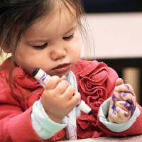 Photo -  Sophie Alexander is more interested in coloring her hand while her older sister, Ella, 4, attends a session of Tiny Tuesdays at the Oklahoma City Museum of Art.    Photo by Jim Beckel, The Oklahoman  Jim Beckel - THE OKLAHOMAN