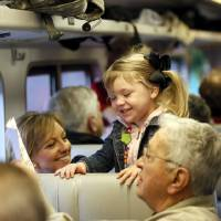 Photo - Rosalee Thompson, 3, of Bixby, Okla., smiles with her grandmother Lana Neafus and great grandfather Paul Neafus on a demonstration ride of the Eastern Flyer passenger train from Sapulpa to the Oklahoma City metro area, Sunday, Feb. 23, 2014. Photo by Nate Billings, The Oklahoman