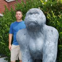 Photo - AUCTION: Willie Ng, head Commerce football coach,  beside the Picher Gorilla statue in front of the main enterance of the high school.   Willie was the football quarterback in 1984 and won the state championship.  The gorilla is one of many items to be  auctioned off starting Sunday at 11:00 a.m.  Photo by Gary Crow, for The Oklahoman                              ORG XMIT: KOD