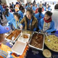 Photo - Wellesley College student Tiffany Liao, of San Marino, Calif., center, serves a pasta dish during a Boston Marathon pre-race dinner at Boston City Hall, Sunday, April 20, 2014, in Boston. With an expanded field of runners and the memory of last year's bombings the 2014 Boston Marathon could bring an unprecedented wave of visitors to the area. (AP Photo/Steven Senne)