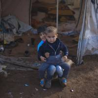 Photo -   Two Syrian boys who fled with their family from the violence in their village, sit in front of a tent at a displaced camp, in the Syrian village of Atma, near the Turkish border with Syria. Saturday, Nov. 10, 2012. (AP Photo/ Khalil Hamra)