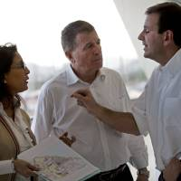 Photo - Rio de Janeiro's Eduardo Paes, right, talks with Nawal El Moutawakel, head of the International Olympic Committee (IOC) Evaluation Commission, center, and International Olympic Committee (IOC) Executive Director for the Olympic Games, Gilbert Felli during a visit to the Olympic Park in Rio de Janeiro, Brazil, Thursday, March 20, 2014. With IOC officials in Rio de Janeiro on to monitor progress on the 2016 Olympics, the city's mayor acknowledged that work on a large cluster of venues is far behind schedule. Paes made his remarks as Nawal El Moutawakel reminded Rio officials that the recent Sochi Winter Olympics showcased