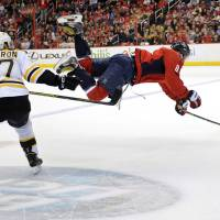 Photo - Washington Capitals right wing Alex Ovechkin (8), of Russia, goes airborne after he was tripped up by Boston Bruins center Patrice Bergeron (37) during the first period of an NHL hockey game, Saturday, March 29, 2014, in Washington. (AP Photo/Nick Wass)