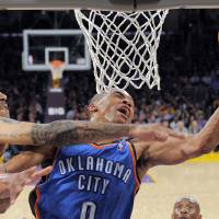 Photo - Oklahoma City Thunder guard Russell Westbrook, right, puts up a shot as Los Angeles Lakers forward Matt Barnes defends during the first half of an NBA basketball game, Thursday, March 29, 2012, in Los Angeles. (AP Photo/Mark J. Terrill)  ORG XMIT: LAS102