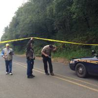 Photo - Investigators leave the scene of a drive-by shooting Tuesday, Aug. 19, 2014 at Bastendorf Beach, Ore. Authorities said a gunman shot five vehicles in a parking lot, killing a Michigan man as he slept, then shot and killed himself. The gunman may also have