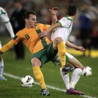 Photo - FILE - In this June 18, 2013, file photo, Australia's Luke Wilkshire, left, is pushed off the ball by Iraq's Mustafa Kareem during their World Cup soccer Asian qualifying match at the Sydney Olympic Stadium in Sydney, Australia. (AP Photo/Rick Rycroft)