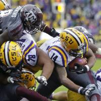 Photo - LSU running back Terrence Magee (14) scores on a touchdown carry as Texas A&M linebacker Steven Jenkins (8) tries to defend in the first half of an NCAA college football game in Baton Rouge, La., Saturday, Nov. 23, 2013. (AP Photo/Gerald Herbert)