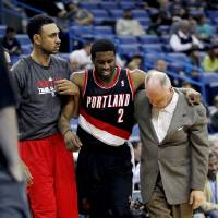 Photo - Portland Trail Blazers guard Wesley Matthews (2) is helped off the court after being injured in the first half of an NBA basketball game against the New Orleans Hornets in New Orleans, Wednesday, Feb. 13, 2013. (AP Photo/Gerald Herbert)