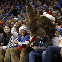 Photo - Rumble sits with fans during an NBA basketball game between the Oklahoma City Thunder and the Toronto Raptors at Chesapeake Energy Arena in Oklahoma City, Sunday, Dec. 22, 2013. Oklahoma City won 107-95. Photo by Sarah Phipps, The Oklahoman