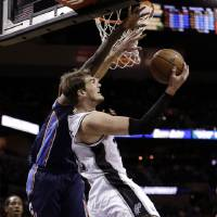 Photo - San Antonio Spurs' Tiago Splitter, right, of Brazil, shoots over Charlotte Bobcats' Michael Kidd-Gilchrist, left, during the first half of an NBA basketball game, Wednesday, Jan. 30, 2013, in San Antonio. (AP Photo/Eric Gay)