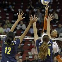 Photo - Texas outside hitter Bailey Webster uses her finger tips to avoid the double-block attempt by Michigan's Krystalyn Goode (12) and Claire McElheny (14) during the national semifinals of the NCAA college women's volleyball tournament semifinal in Louisville, Ky., Thursday, Dec. 13, 2012.  (AP Photo/Garry Jones)