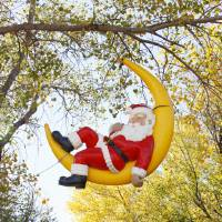 Photo - Santa reclines in a sliver of moon hanging from a tree at Chisholm Trail Park in Yukon.