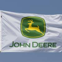 Photo -   In this Aug. 31, 2011 photo, a flag displaying the John Deere logo flies at the John Deere farming equipment exhibit area during the Farm Progress Show in Decatur, Ill. Deere & Co., the world's largest maker of agricultural equipment, reported a bigger fourth-quarter profit Wednesday, Nov. 21, 2012, as it sold more equipment at higher prices, but results still missed analyst expectations. (AP Photo/Seth Perlman)