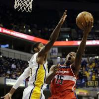 Photo - Washington Wizards guard Jordan Crawford (15) shoots around Indiana Pacers forward Paul George (24) during the first half of an NBA basketball game, Wednesday, Jan. 2, 2013, in Indianapolis. (AP Photo/AJ Mast)