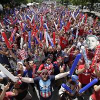 Photo - United States fans cheer while watching before the start of the 2014 World Cup soccer match between the United States and Belgium at a public viewing party, in Detroit, Tuesday, July 1, 2014. (AP Photo/Paul Sancya)